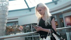 Stående av en härlig ung kvinna som använder ett smartphoneanseende vid ett glass fönster för modelagerskärm med dvärgar stock video