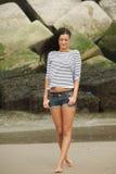 Stående av en härlig ung kvinna som går på en sandig strand royaltyfri bild
