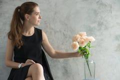 Stående av en härlig ung kvinna som kopplar av med blomman i vardagsrum bilder för tappningeffektstil Royaltyfria Foton