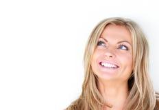 Stående av en härlig ung kvinna som ler och ser upp Royaltyfri Bild