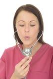 Stående av en härlig ung kvinnlig doktor Blowing Down en stetoskop Royaltyfria Bilder