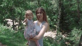 Stående av en härlig ung moder med hennes dotter i skogen, på en bakgrund av en bergflod, närbild lager videofilmer