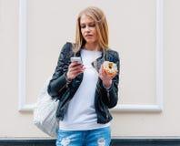 Stående av en härlig ung sexig kvinna som äter en munk, blickar på hennes smarta telefon på gataeuropéstaden utomhus- Arkivfoton