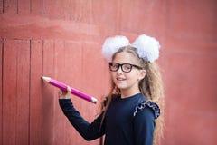 Stående av en härlig ung skolflicka Avsked Klocka Dag av kunskap Början av skolåret royaltyfri foto