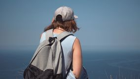 Stående av en härlig ung turist- flicka, blickar på en fyr, med en ryggsäck, i en sugrörhatt, lager videofilmer