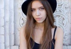 Stående av en härlig ung vuxen flicka i den utomhus- svarta hatten Arkivbilder