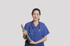 Stående av en hållande skrivplatta för asiatisk kvinnlig sjuksköterska över grå bakgrund Arkivbild