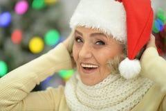 Stående av en hög kvinna i jultomtenhatt arkivbild