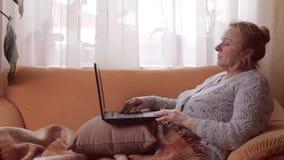 Stående av en hög kvinna som arbetar på bärbara datorn lager videofilmer