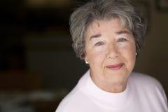 Stående av en hög kvinna som ler på kameran Fotografering för Bildbyråer