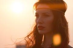 Stående av en hippiekvinna med huvudbindeln som långt borta ser på solnedgången med blåsigt hår Arkivbilder