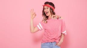 Stående av en hipsterflicka med tatueringen, på rosa bakgrund royaltyfri foto