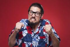 Stående av en ilsken ung man i hawaiansk skjorta med gripen hårt om fi Arkivfoton
