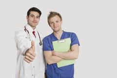 Stående av en indisk doktor som gör en gest upp tummar, medan stå med sjukskötaren över ljus - grå bakgrund Fotografering för Bildbyråer