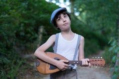 Stående av en ironisk pojke med en mandolin Fotografering för Bildbyråer