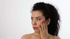 Stående av en kvinna för lockigt hår som trycker på hennes framsida stock video