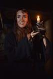 Stående av en kvinna i mörkret med en stearinljus Arkivbild