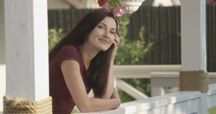Stående av en kvinna med det positiva leendet som ser kameran med ljus framtid som står på det vita Terrasse skottet på rött arkivfilmer