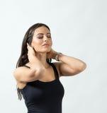 Stående av en kvinna med stängda ögon som trycker på hennes hals royaltyfri foto