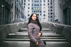 Stående av en kvinna på ett affärstema Den unga Caucasian brunettflickan i det långa omslaget, lag med den svarta läderpåsen står fotografering för bildbyråer