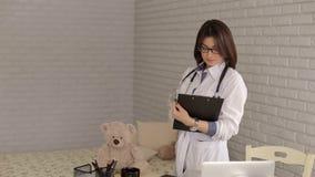 Stående av en kvinna som är pediatrisk i exponeringsglas och en vit ämbetsdräkt och anteckningsbok arkivfilmer