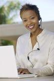 Stående av en kvinna som använder bärbara datorn och hörlurar med mikrofon på uteplats Arkivfoto