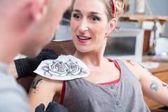 Stående av en kvinna som får en ny tatuering i en yrkesmässig studio royaltyfri bild