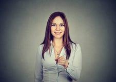 Stående av en kvinna som ler och pekar på kameran Arkivfoto