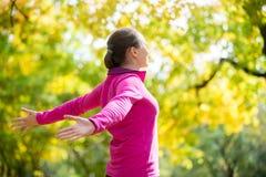 Stående av en kvinna utomhus i en sportswear, outstreched händer arkivfoton