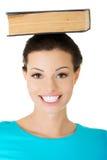 Stående av en kvinnainnehavbok på hennes huvud fotografering för bildbyråer