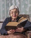 Stående av en läsning för gammal kvinna Arkivfoton