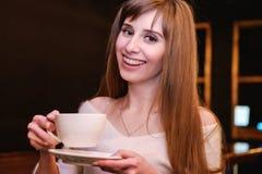 Stående av en långhårig härlig flicka i en vit tröja En flicka står i en coffee shop på en trätabell och rymmer en kopp av arkivfoton