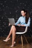 Stående av en le affärskvinna med bärbar datorsammanträde på vindutrymme Royaltyfri Fotografi