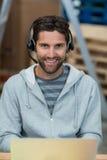Stående av en le arbetare som bär en hörlurar med mikrofon royaltyfri bild
