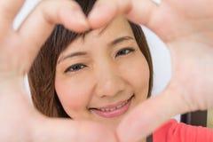 Stående av en le asiatisk flicka med ramhänder Royaltyfri Foto