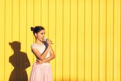 Stående av en le flicka med glass i händer på en gul bakgrund Royaltyfri Fotografi