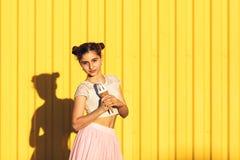 Stående av en le flicka med glass i händer på en gul bakgrund Arkivbild
