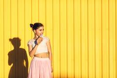 Stående av en le flicka med glass i händer på en gul bakgrund Arkivfoton