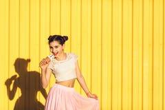 Stående av en le flicka med glass i händer på en guling b Royaltyfri Bild