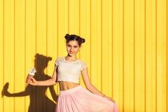 Stående av en le flicka med glass i händer på en guling b Arkivbilder
