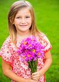 Stående av en le gullig liten flicka med blommor Arkivfoton