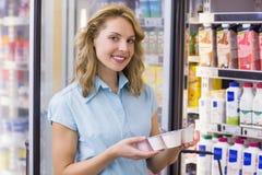Stående av en le kvinna som har på hennes händer en ny yoghurt Arkivbilder