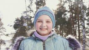 Stående av en le liten flicka i en vinterskog arkivfilmer