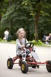 Stående av en le littlelflicka som kör bilen i munterhet Royaltyfri Bild
