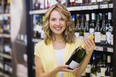 Stående av en le nätt blond kvinna som har en vinflaska Royaltyfri Foto