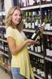 Stående av en le nätt blond kvinna som har en vinflaska i henne händer Arkivbild