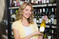 Stående av en le nätt blond kvinna som visar en vinflaska Fotografering för Bildbyråer