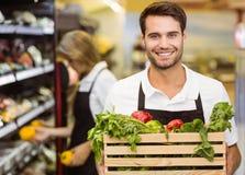 Stående av en le personalman som rymmer en ask av nya grönsaker Royaltyfria Bilder