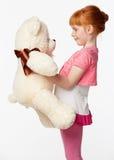 Stående av en le redheaded flicka i rosa krama för skjorta Arkivfoto