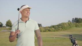 Stående av en le säker lyckad mitt - östlig man med ett golfklubbanseende på en golfbana i bra soligt arkivfilmer